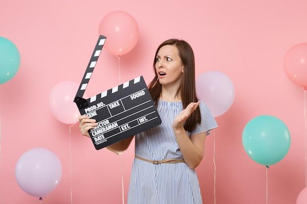 Портрет обеспокоенной женщины в синем платье, разводящей руки, глядя в сторону, держащей классический черный фильм, делающий с 'хлопушкой' на розовом фоне с красочными воздушными шарами. концепция вечеринки по случаю дня рождения.