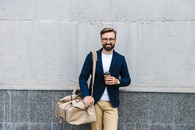 종이 컵에서 커피를 마시고 벽 근처에 서있는 동안 가방을 들고 안경을 쓰고 자신감 사업가의 초상화