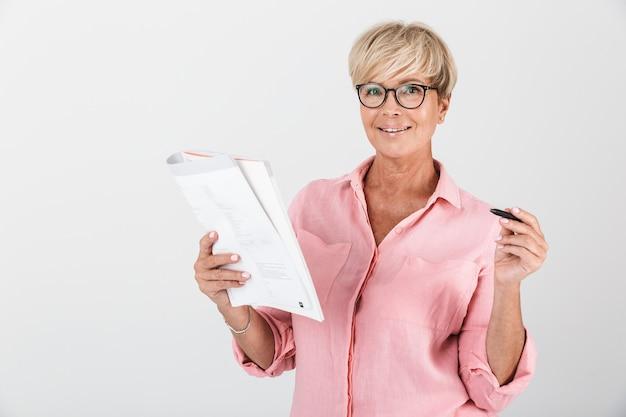 Портрет уверенно взрослой женщины в очках, держащей учебную книгу и ручку, изолированную над белой стеной в студии