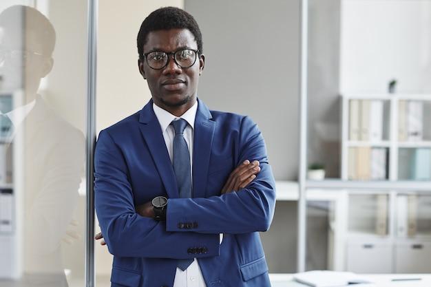 Портрет уверенного африканского лидера в костюме, стоя в офисе