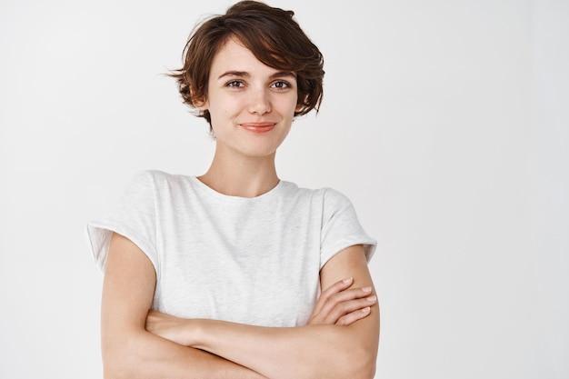 Портрет уверенной и счастливой женщины с короткими волосами, скрестив руки на груди, как профессионал и улыбающейся, стоящей у белой стены