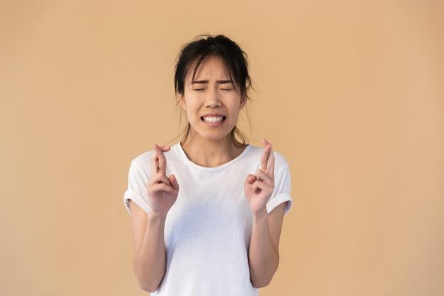 神を懇願する基本的なtシャツを着ている自信を持ってアジアの女性の肖像画は、スタジオでベージュの壁の上に分離された指を交差させてください