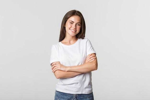 Портрет уверенно привлекательной женщины, скрещенными на груди руками и довольной улыбкой.