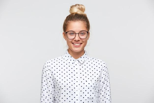 Портрет уверенно привлекательной молодой женщины с булочкой носит рубашку в горошек и очки