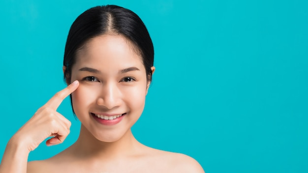 얼굴에 눈 옆에 손으로 스튜디오 샷 파란색 배경에 고립 웃 고 자신감이 아름 다운 아시아 여자의 초상화. 건강한 얼굴 개념에 대한 스킨 케어.