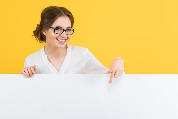 Портрет уверенно красивая молодая деловая женщина, показывая пустой рекламный щит на желтом фоне