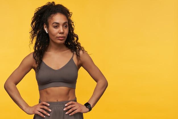 自信を持って美しい若いフィットネス女性が立って、黄色い壁にワイヤレスイヤホンとスマートウォッチを使っているポートレート