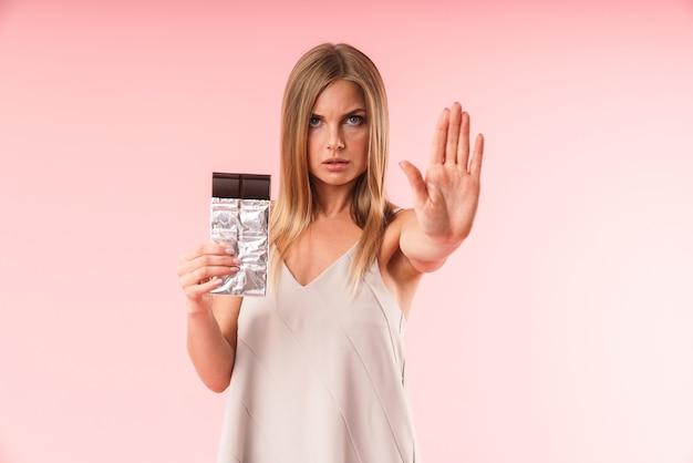 スタジオでピンクの壁に隔離されたチョコレートバーを保持しながら、拒否で身振りで示すドレスを着ている自信を持って金髪の女性の肖像画