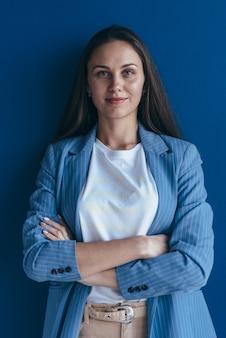 Портрет уверенно деловой женщины стоя, прислонившись к стене.