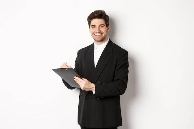 Портрет уверенно бизнесмена в черном костюме, подписывая документы и улыбаясь, стоя счастливым на белом фоне.