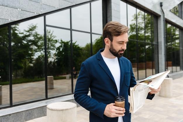 Портрет уверенного бизнесмена в куртке, пьющего кофе из бумажного стаканчика и читающего газету, стоя на открытом воздухе возле здания