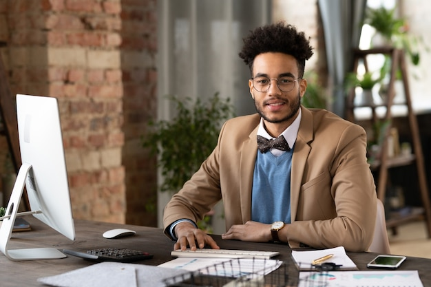 Портрет уверенно бизнесмена, улыбаясь в камеру, сидя на своем рабочем месте в офисе с компьютером и документами