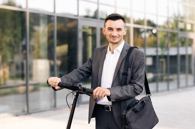 Портрет уверенно бизнесмена, стоящего с электросамокатом и смотрящего на технолога камеры
