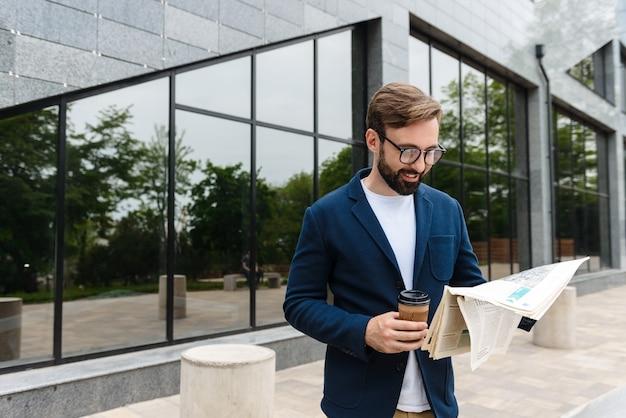 Портрет уверенного бизнесмена в очках, пьющего кофе из бумажного стаканчика и читающего газету, стоя на открытом воздухе возле здания