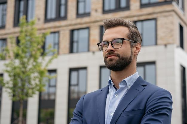 Портрет уверенно бизнесмена в костюме и стильных очках, стоящих на открытом воздухе