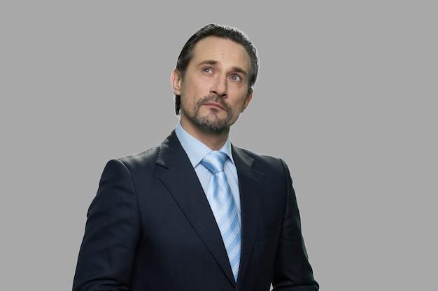 思いやりのある表現で自信を持ってビジネスマンの肖像画。灰色の背景に対して物思いにふける立っているように見えるビジネススーツの男の肖像画。