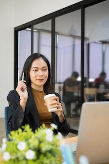 コーヒーカップを保持し、ラップトップコンピューターで彼女のビジネスパートナーとビデオ通話をしている自信を持って実業家の肖像画。