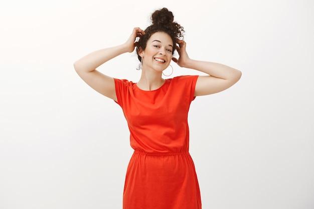 빗질 곱슬 머리를 가진 자신감이 평온한 유럽 여성의 초상화, 머리에 손을 잡고 긍정적으로 웃고