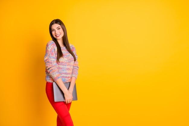 Портрет уверенной довольной мечтательной девушки, держащей компьютер, чувствует себя удовлетворенной, носить осенний пуловер, изолированный на ярком цвете