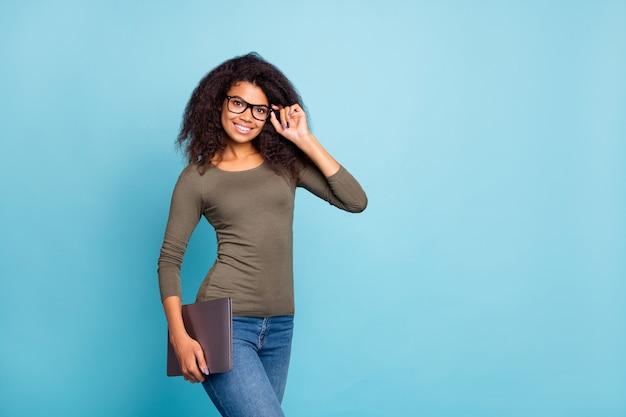 자신감이 멋진 관리자 아프리카 미국 여자의 초상화는 파란색 벽 위에 절연 트렌디 한 녹색 스웨터 데님 청바지를 착용 할 준비가 된 독립적 인 터치 안경 안경 보류 노트북을 느낍니다.