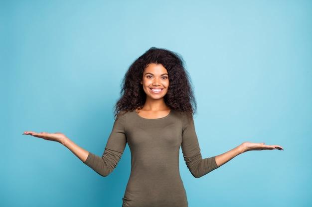 自信を持ってクールなムラートの女の子の肖像画は手を握る本物のプロモーター現在の販売オファー選択するアドバイス広告を着る青い色の壁に隔離されたカジュアルなスタイルの服