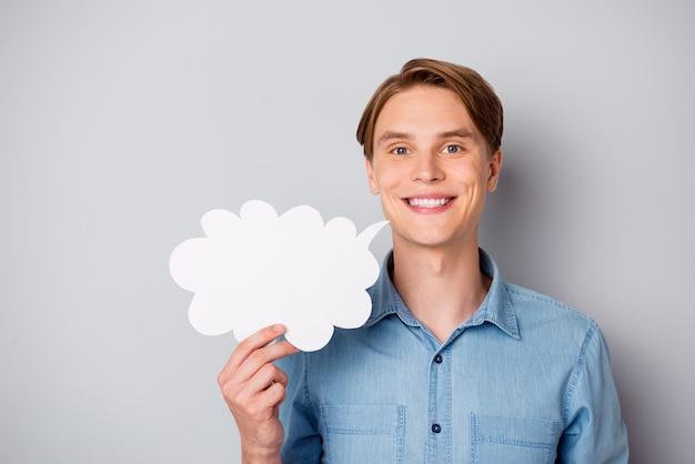 Портрет уверенной в себе крутой позитивной девушки, держащей белую бумажную карточку, пузырь, делится своей точкой зрения, носит красивый наряд, изолированный на сером цветном фоне