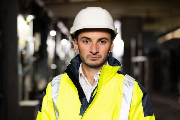 建設現場の自信を持って電気技師の若年労働者専門の立っている廊下の肖像画