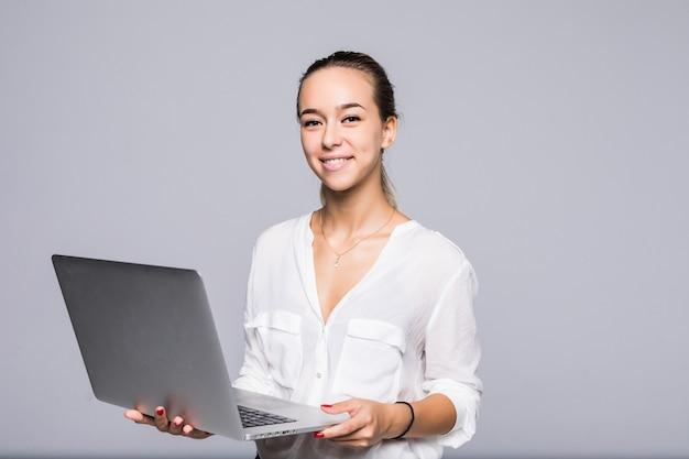 회색 벽에 고립 된 작업을 위해 현대 노트북을 사용하는 자신감 경험이 풍부한 영리한 지적인 여자의 초상화