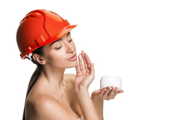 주황색 헬멧에 자신감 여성 행복 미소 작업자의 초상화. 흰색 스튜디오 배경에 고립 된 여자입니다. 미용, 화장품, 스킨 케어, 피부 및 얼굴 보호, 미용 및 크림 개념