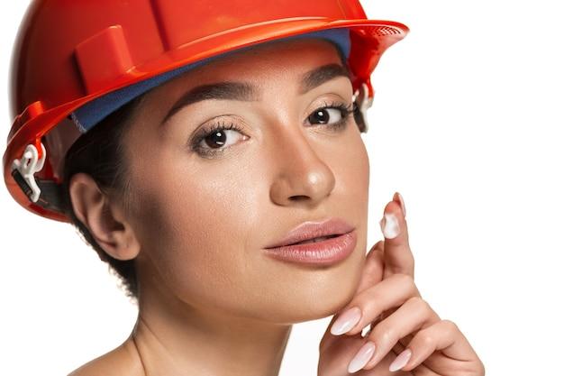 オレンジ色のヘルメットをかぶった自信に満ちた女性の幸せな笑顔の労働者のポートレート。ホワイト スタジオの背景に分離された女性。美容、化粧品、スキンケア、肌と顔の保護、美容、クリームのコンセプト