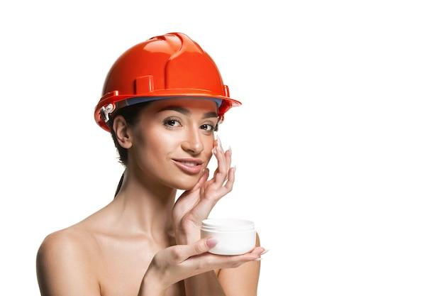 オレンジ色のヘルメットで自信を持って女性の幸せな笑顔の労働者の肖像画。白い壁に隔離された女性。美容、化粧品、スキンケア、肌と顔の保護、美容とクリームのコンセプト