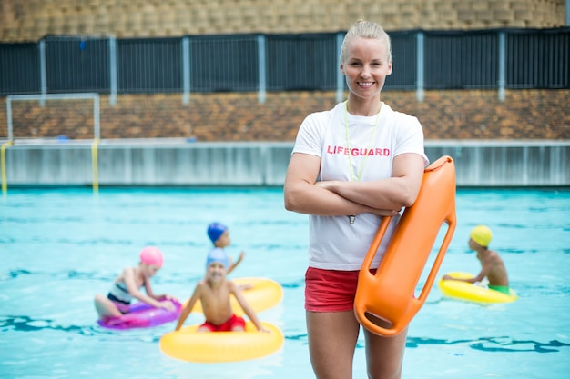 プールサイドで救助缶と立っている自信を持って女性のライフガードの肖像画