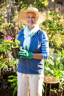 Портрет уверенно садовник с горшечных растений в саду