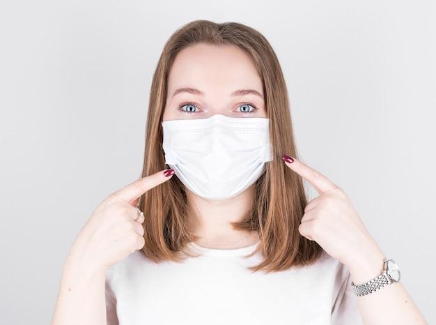 자신감이 소녀 포인트 의료 마스크의 초상화는 회색에 고립 된 새로운 안전 covid-19 보호 착용 캐주얼 스타일 복장을 나타냅니다