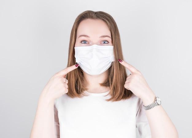 자신감이 소녀 포인트 의료 마스크의 초상화는 회색 배경 위에 절연 새로운 안전 covid-19 보호 착용 캐주얼 스타일 복장을 나타냅니다.