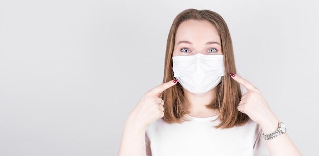 Портрет уверенной девушки в медицинской маске указывает на новую безопасную одежду для защиты от covid-19 в повседневном стиле, изолированную на сером цветном фоне