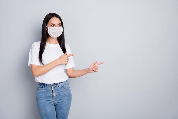 자신감이 소녀 발기인 포인트 검지 손가락 copyspace 모습의 초상화는 covid19 보호 착용 tshirt 데님 청바지 의료 마스크 절연 회색 배경을 보여줍니다