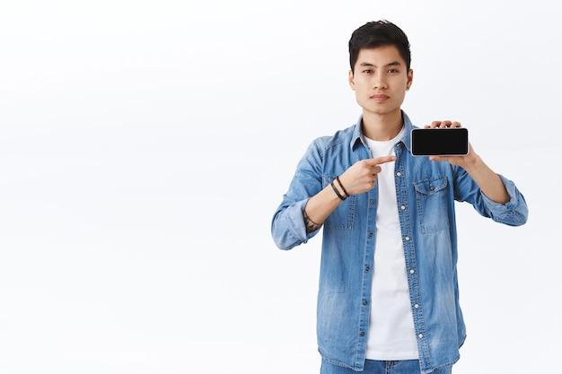 스마트폰 화면에 앱 또는 회사 홍보를 보여주는 자신감 있고 잘 생긴 아시아 남성의 초상화, 다운로드를 권장하는 휴대전화를 가리키는