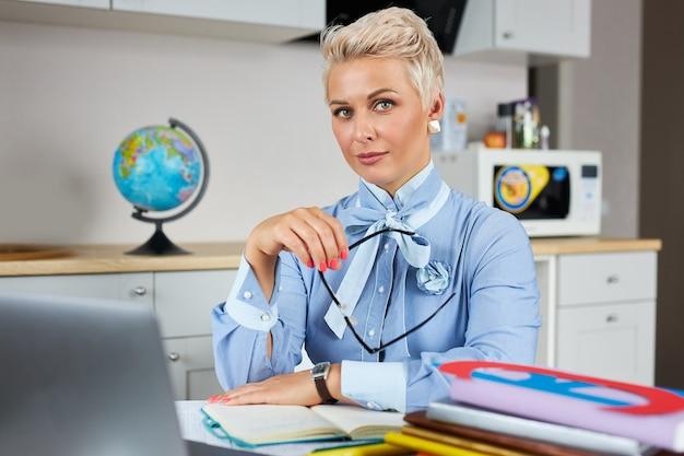 Портрет уверенно красивого учителя, сидящего за столом