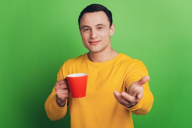 自信を持って男の肖像画は、緑の背景にあなたを指してコーヒーを飲みます