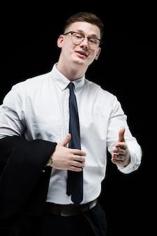 黒の背景に親指で自信を持ってハンサムな野心的な笑みを浮かべてエレガントな責任ある実業家の肖像画