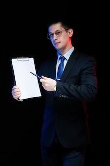 Портрет уверенно красивый стильный бизнесмен, держа в руках буфера обмена на черном фоне