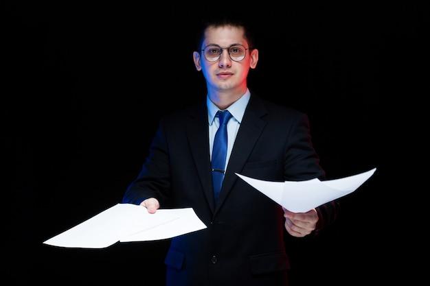 Портрет уверенно красивый стильный бизнесмен держит бумаги в его руках черный