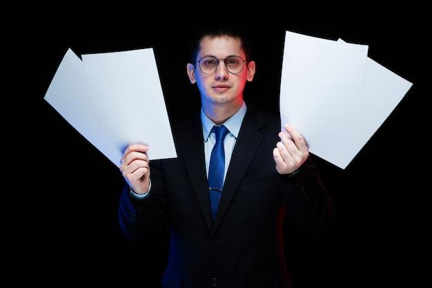 Портрет уверенно красивый стильный бизнесмен держит бумаги в руках на черном фоне