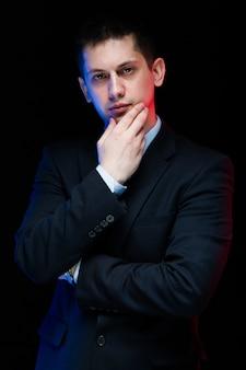 Портрет уверенно красивый стильный бизнесмен, касаясь его подбородка