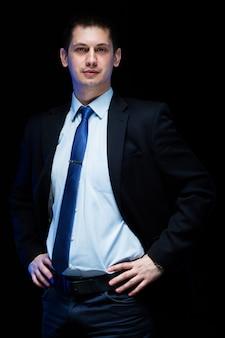 Портрет уверенно красивый стильный бизнесмен с руками его пояс на черном