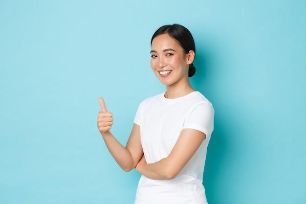 自信を持って幸せな笑顔、承認で親指を示す白いtシャツの美しいアジアの少女の肖像画、何かを奨励し、許可を与え、青い壁に満足