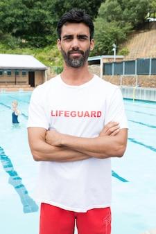 Портрет уверенно спасателя, стоящего со скрещенными руками у бассейна