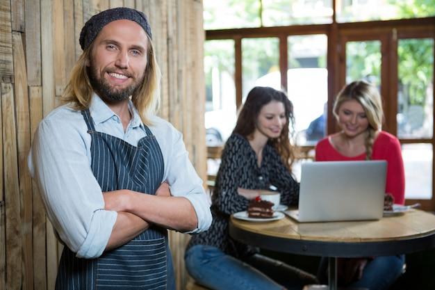 カフェでバックグラウンドで女性顧客と自信を持って男性バリスタの肖像画