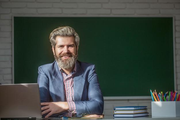 교실에서 자신감 있는 남자 교사의 초상화입니다. 수업 시간에 노트북을 들고 있는 젊은 남자 교사는 교실 칠판에 앉아 있다. 초등학교 교실에서 웃는 선생님